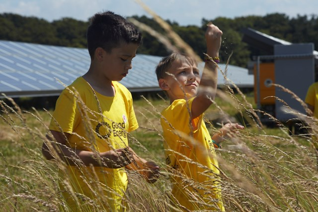 School boys in a field with solar panels