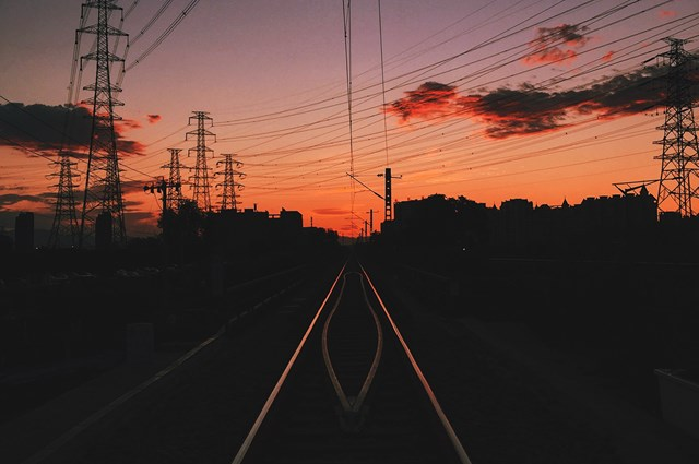 Pylons and train tracks at sunset.