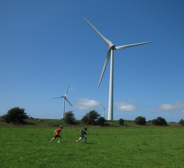 Wind turbines with boys at play